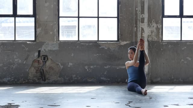 vídeos de stock e filmes b-roll de a young woman in yoga outfit stretching her body indoors - claraboia