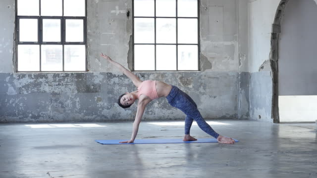 a young woman in yoga outfit stretching her waist indoors - ärmelloses oberteil stock-videos und b-roll-filmmaterial