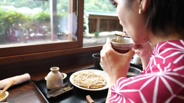 young woman in yukata eating japanese soba for lunch - japanese food stock videos & royalty-free footage