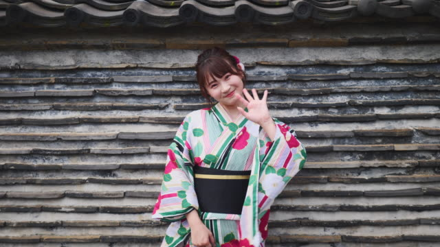 young woman in yukata leaning on wall - yukata robe stock videos & royalty-free footage