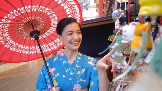 young woman in yukata looking at japanese wind chimes (windbells) in shopping mall - yukata robe stock videos & royalty-free footage