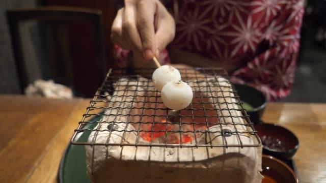 young woman in yukata putting dango dumpling on hibachi grill - yukata video stock e b–roll