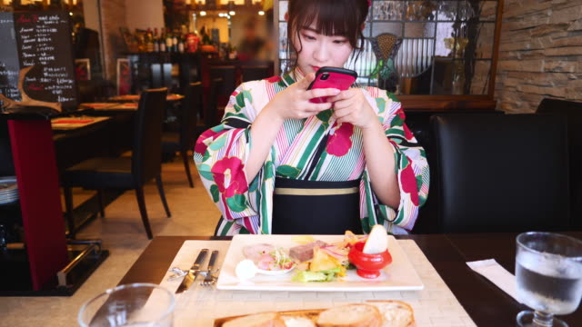 young woman in yukata taking photos of french food for lunch - french food stock videos & royalty-free footage