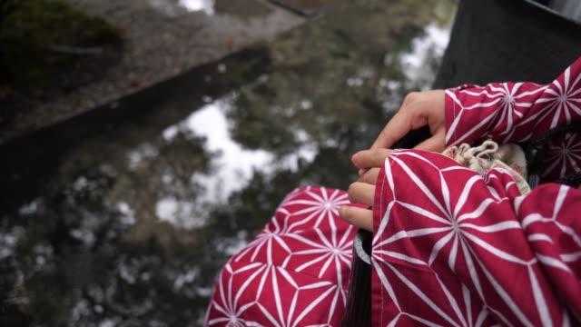 young woman in yukata waiting for rain to stop - yukata video stock e b–roll