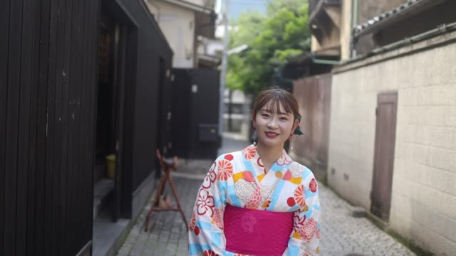 young woman in yukata walking on narrow path - kimono stock videos & royalty-free footage