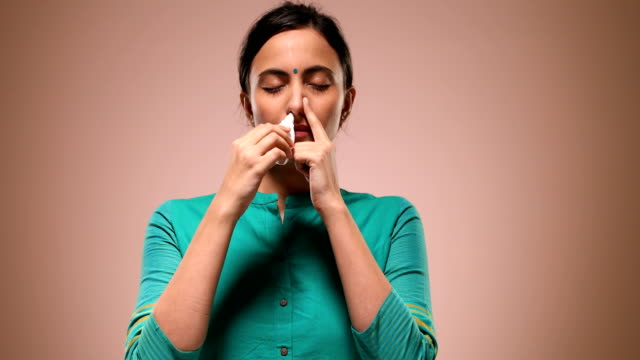 CU Young woman inhaling nasal spray while standing against pink background / New Delhi, Delhi, India