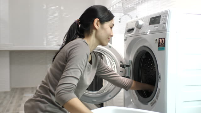 young woman input clothing clean laundry from the tumble dryer at home - appliance stock videos & royalty-free footage
