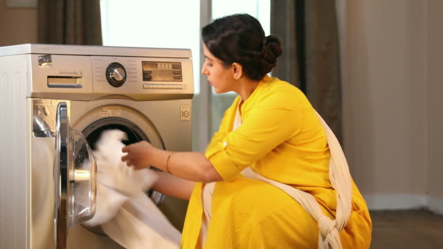 ms young woman inserting clothes inside the washing machine at home / delhi, india - routine stock videos & royalty-free footage