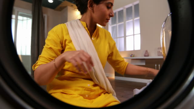 cu young woman inserting clothes inside the washing machine at home / delhi, india - washing stock videos and b-roll footage