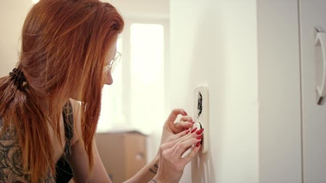 vidéos et rushes de interrupteur d'éclairage installation jeune femme - interrupteur