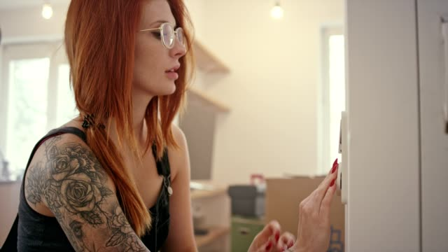 young woman installing light switch - redhead stock videos & royalty-free footage