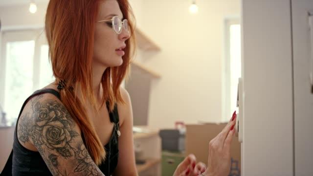 stockvideo's en b-roll-footage met jonge vrouw installeren lichtschakelaar - roodhoofd