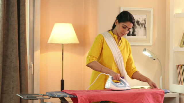 ms young woman ironing clothes on ironing board at home / delhi, india - ironing board stock videos & royalty-free footage