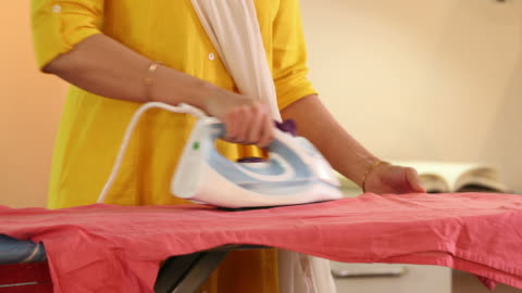 cu young woman ironing clothes on ironing board at home / delhi, india - アイロン台点の映像素材/bロール