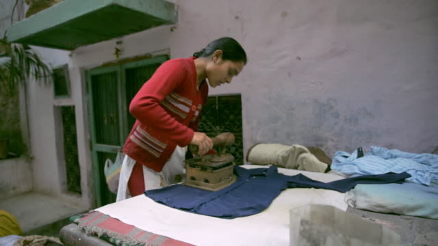 a young woman irons laundry, india - bügelbrett stock-videos und b-roll-filmmaterial