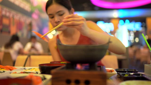 Young woman is eating Japanese food.