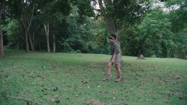 vídeos y material grabado en eventos de stock de mujer joven está explorando el bosque en un día hermoso. - espalda humana