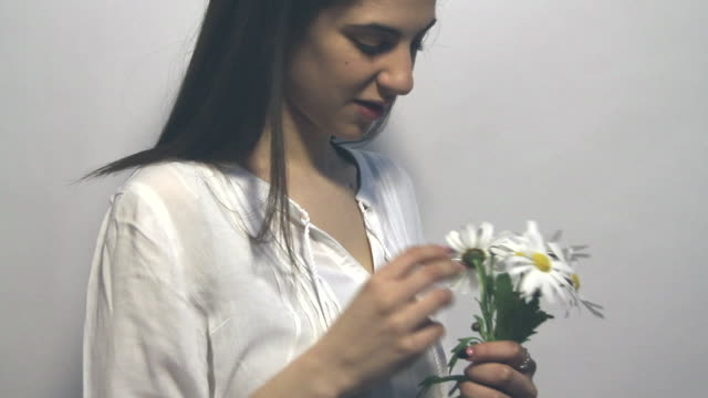 young woman is holding a bunch of flowers