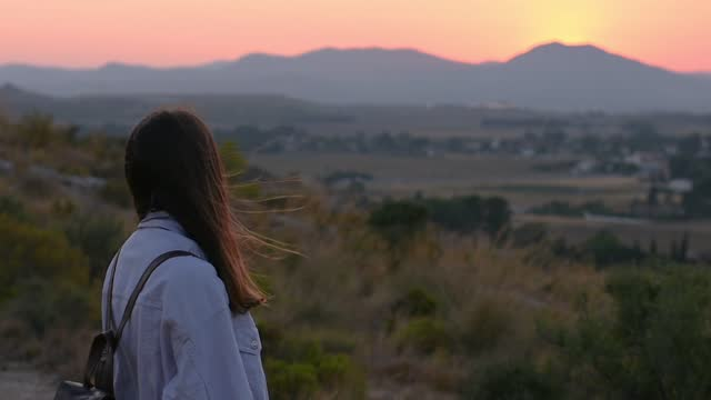 Young woman is looking to the mountain and the last lights of sun