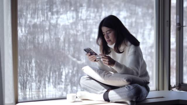 若い女性は銀行カードを持って支払いを行い、自宅の窓の近くのテラスに座ってスマートフォンで作業しています。オンライン、インターネット、近代的な技術の概念を購入します。 - アジア大陸点の映像素材/bロール