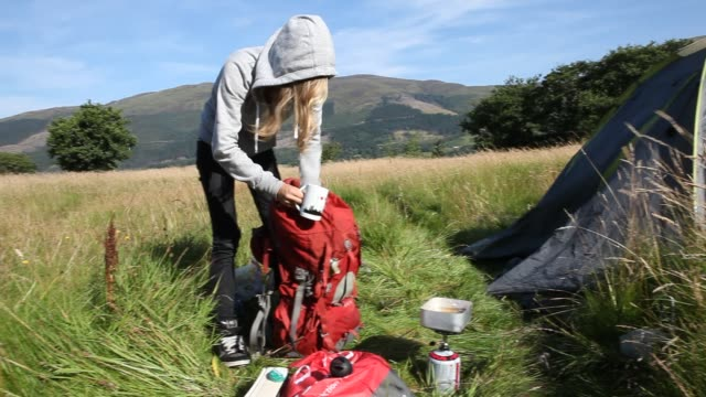 young woman is packing her backpack in front of a tent near loch leven in glencoe in the scottish highlands, smoking a cigarette and preparing food... - camping stock videos & royalty-free footage