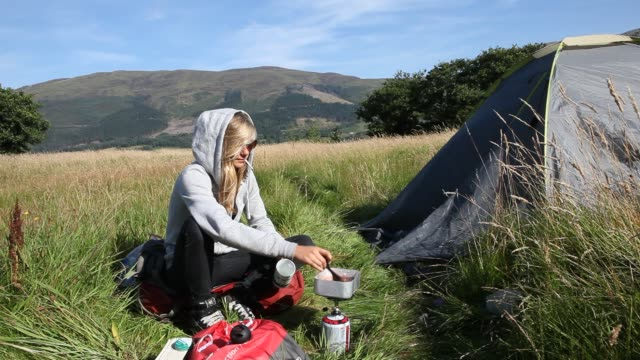 stockvideo's en b-roll-footage met a young woman is packing her backpack in front of a tent near loch leven in glencoe in the scottish highlands smoking a cigarette and preparing food... - rugzak