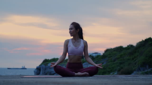 young woman is practicing yoga at mountain sea. - zen like stock videos & royalty-free footage