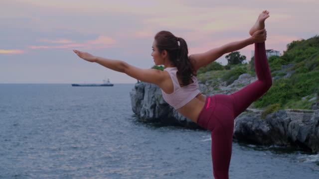 vídeos y material grabado en eventos de stock de joven es practicar yoga en el mar de la montaña. - oriental asiático e indio