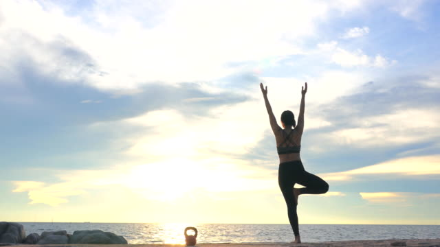 young woman is practicing yoga on the beach at sunset. - lotus position stock videos & royalty-free footage