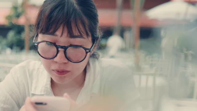 vídeos de stock, filmes e b-roll de jovem é compras on-line usando um smartphone. - trabalhadora de colarinho branco