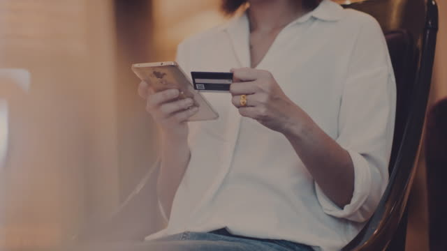 young woman is shopping online using a smartphone. - paying card stock videos & royalty-free footage