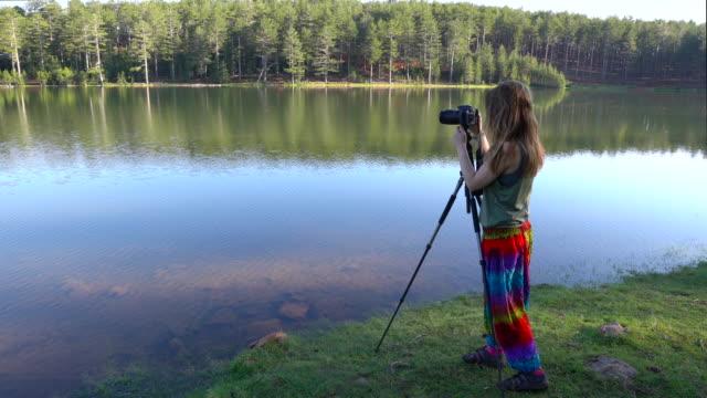 若い女性は寒い朝に純粋な自然の中で湖で写真撮影をしています - デジタル一眼レフカメラ点の映像素材/bロール