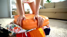 A young woman is trying to close a chock-full orange suitcase. Time lapse