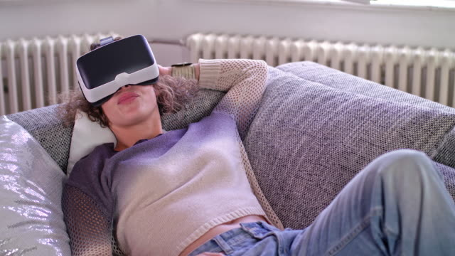 young woman is using her vr headset while lying on a couch - lying on back stock videos & royalty-free footage