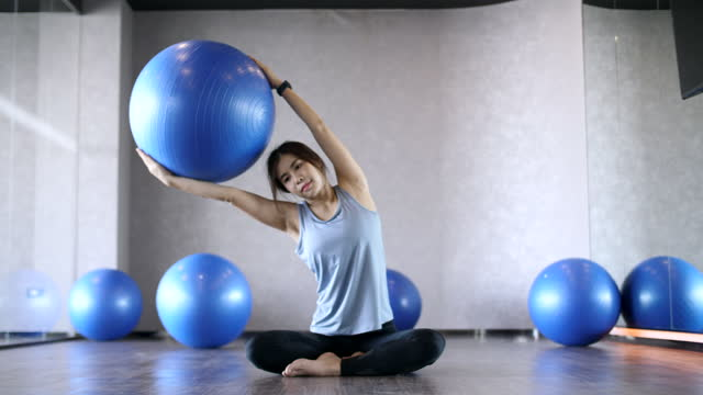 young woman is using phone while relaxing - fitness ball stock videos & royalty-free footage
