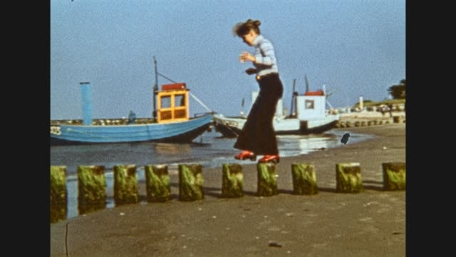 young woman is walking along the beach of the baltic sea / views to cutters lying at the beach and several beach chairs / woman balancing over wooden... - ロマンチックな空点の映像素材/bロール