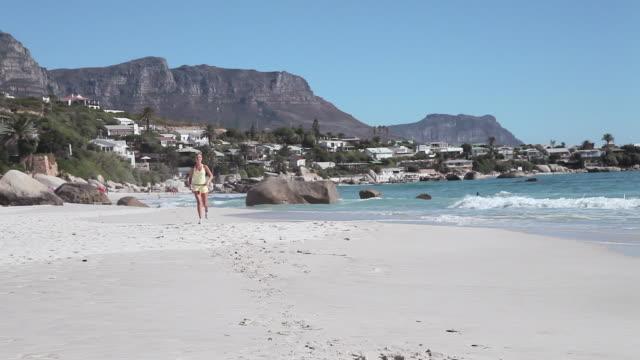 stockvideo's en b-roll-footage met young woman jogging on beach - gymbroek