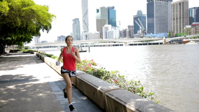 young woman jogging on brisbane southbank - riverbank stock videos & royalty-free footage