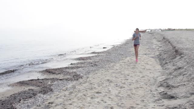 young woman jogging on the beach - cura della persona video stock e b–roll