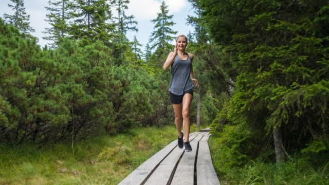 Young woman jogging through forest among lush green trees on a beautiful day