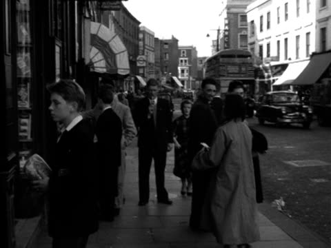 young woman joins a group of people looking at an accomodation notice board on the exterior of a shop. 1956. - number of people stock videos & royalty-free footage