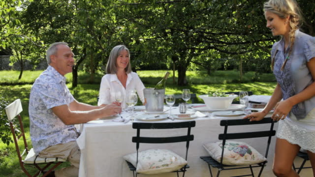 WS Young woman joins in parents at table in garden / London, United Kingdom