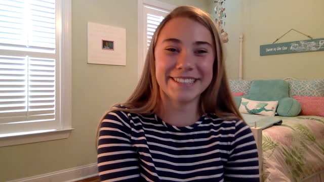 a young woman joyfully nods and participates in zoom class from home - webcam video stock e b–roll