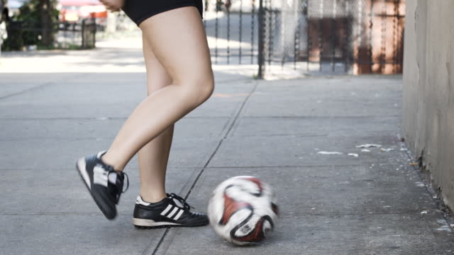 vídeos de stock, filmes e b-roll de a young woman juggles a soccer ball on a new york street - closeup - slow motion - 4k - determinação
