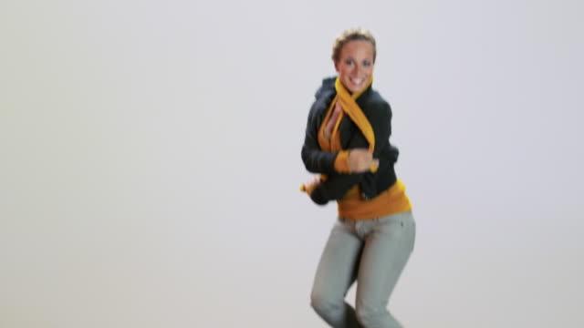 vídeos de stock e filmes b-roll de young woman jumping and throwing leaves, slow motion - trampolim equipamento desportivo