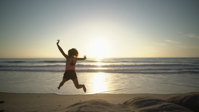WS SM Young woman jumping for joy on the beach
