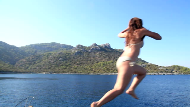 Young woman jumping from boat into sea