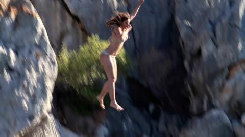 vídeos y material grabado en eventos de stock de joven mujer salto desde acantilado en el mar - deporte de riesgo