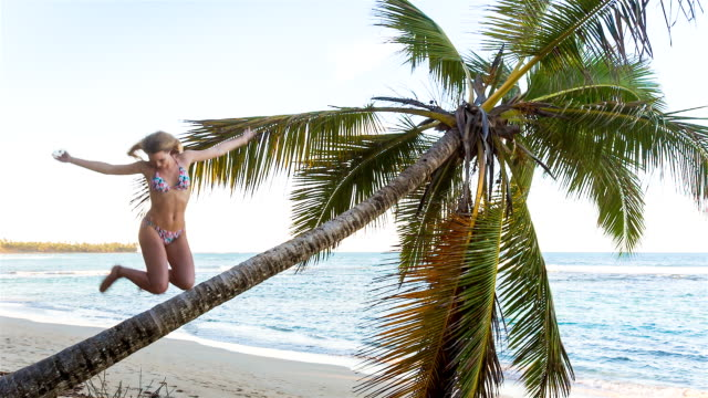 MS young woman jumping from palm tree at tropical beach