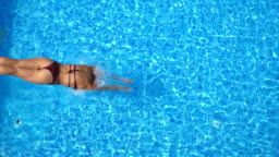 Young woman jumping in pool and splashing crystal clear water. Unrecognizable girl swimming under water in basin of hotel at sunny day. Lady relaxing during summer vacation. Slow motion Top view